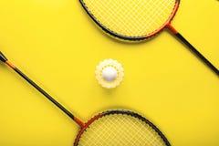 Federball und Schläger für das Spielen von Badminton auf einem gelben Hintergrund minimalismus Konzeptsommer razlecheny stockbild