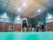 Federballplatz mit abgegratenem Spielerbadminton Stockbilder