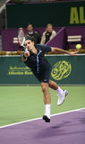 Federer runs for the ball in Qatar. DOHA, QATAR - JAN 7, 2009: Swiss superstar Roger Federer dives for the ball during his second-round match Against Andreas Royalty Free Stock Photos
