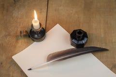 Federkiel und Tintenfaß und Kerzenständerbrunnen, der auf altem Papier stillsteht Feder auf dunklem Hintergrund gegen alte Bücher Stockbilder