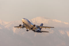 FedEx Federal Express Airbus A310 cargo aircraft taking off in front of snow capped mountains. Royalty Free Stock Photos