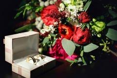 Fedi nuziali catturate con i fiori sui precedenti Fotografie Stock