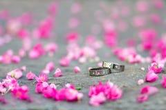 Fedi nuziali d'argento e fiori rosa sui precedenti di pietra Fotografia Stock