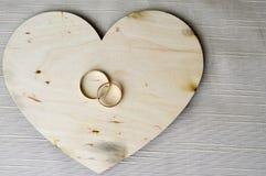 Fedi nuziali dell'oro su un cuore di legno Luminoso, brillando, cuori affascinanti, alla moda, costosi fatti di legno con gli orn Immagini Stock