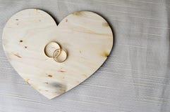 Fedi nuziali dell'oro su un cuore di legno Luminoso, brillando, cuori affascinanti, alla moda, costosi fatti di legno con gli orn Fotografia Stock