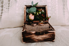 Fedi nuziali dorate nella bella scatola rustica con i fiori interno e sui precedenti leggeri Fotografie Stock Libere da Diritti