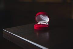 Fedi nuziali dorate in scatola rossa sulla tavola nera immagini stock