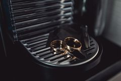 Fedi nuziali dorate su una macchina cromata del caffè Fotografia Stock Libera da Diritti