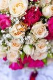 Fedi nuziali dorate sul mazzo di nozze di pallido - rosa e cremisi o rose rosse Fotografia Stock Libera da Diritti