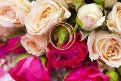 Fedi nuziali dorate sul mazzo di nozze di pallido - rosa e cremisi o rose rosse Immagine Stock Libera da Diritti