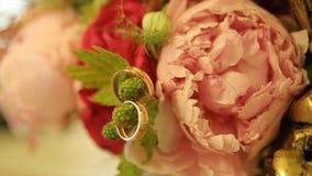 Fedi nuziali e mazzo della rosa di rosa Fedi nuziali su un mazzo di nozze Fedi nuziali su un mazzo delle rose Fotografie Stock Libere da Diritti