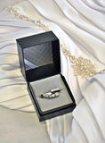 Fedi nuziali in scatola con il fondo del vestito da sposa Fotografie Stock