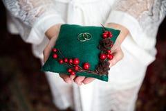 Fedi nuziali su un cuscino nelle mani di una donna fotografie stock libere da diritti