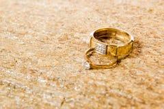 Fedi nuziali su una pietra naturale con le inclusioni di oro indigeno Mani e cuori di offerta Fotografie Stock Libere da Diritti
