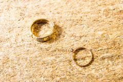 Fedi nuziali su una pietra naturale con le inclusioni di oro indigeno Mani e cuori di offerta Immagine Stock