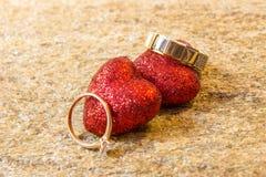 Fedi nuziali su una pietra naturale con le inclusioni di oro indigeno Mani e cuori di offerta Fotografia Stock Libera da Diritti