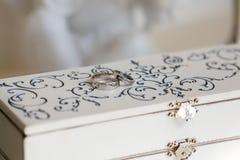 Fedi nuziali su una scatola d'annata bianca Immagine Stock