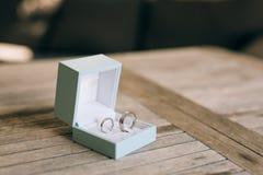 Fedi nuziali su una struttura di legno leggera in una scatola blu Nozze J Fotografia Stock