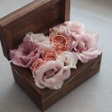 Fedi nuziali sui fiori in vecchia scatola di legno rustica per cerimonia di nozze Immagini Stock Libere da Diritti