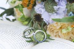 Fedi nuziali sul libro e sui fiori Fotografia Stock