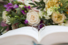 Fedi nuziali sul libro e sui fiori Immagine Stock
