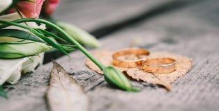 Fedi nuziali sull'arancia, permesso dell'oro di autunno Fotografia Stock
