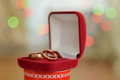Fedi nuziali in un contenitore di regalo rosso con un bokeh del fondo del partito di scintillio immagini stock