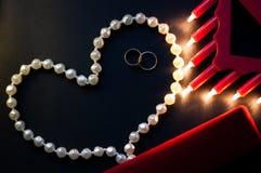 Fedi nuziali, una serie di perle su un fondo nero, luci brucianti, una scatola rossa St Giorno del ` s del biglietto di S Immagini Stock