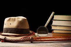 Fedora hat with bullwhip near magnifying glass and old books on black background. Adventure concept Royalty Free Stock Photography