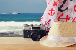 Fedora hat, old vintage camera and scarf over wooden table and sea landscape background. relaxation or vacation concept Stock Photo