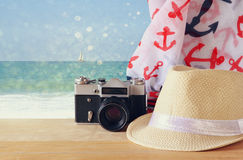 Fedora hat, old vintage camera and scarf over wooden table and sea landscape background. relaxation or vacation concept Stock Photos