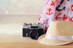Fedora hat, old vintage camera and scarf over wooden table and sea landscape background. relaxation or vacation concept Stock Photography