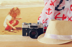 Fedora hat, old vintage camera and scarf over wooden table and sea landscape background. relaxation or vacation concept Stock Images