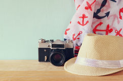 Fedora hat, scarf and old vintage camera over wooden table. relaxation or vacation concept Royalty Free Stock Photography