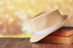 Fedora hat and stack of books over wooden table Stock Photos