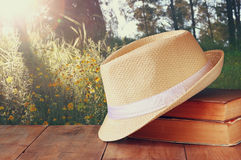 Fedora hat and stack of books over wooden table and evening nature country side background. relaxation or vacation concept Royalty Free Stock Photography