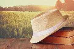 Fedora hat and stack of books over wooden table and field of wheat country side background. relaxation or vacation concept Royalty Free Stock Photo
