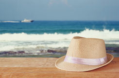 Fedora hat and stack of books over wooden table and sea landscape background. relaxation or vacation concept Royalty Free Stock Photos