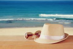 Fedora hat and stack of books over wooden table and sea landscape background. relaxation or vacation concept Royalty Free Stock Image