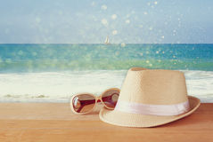 Fedora hat and stack of books over wooden table and sea landscape background. relaxation or vacation concept Royalty Free Stock Photography