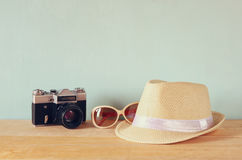Fedora hat, sunglasses old vintage camera over wooden table. relaxation or vacation concept Stock Photo
