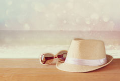 Fedora hat and sunglasses over wooden table and glitter background. relaxation or vacation concept Stock Photos