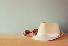Fedora hat and sunglasses over wooden table. relaxation or vacation concept Royalty Free Stock Image