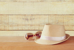 Fedora hat and sunglasses over wooden table. relaxation or vacation concept.  stock photography