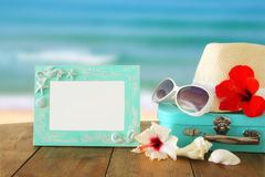 Fedora hat, sunglasses, tropical hibiscus flower next to blank frame over wooden table and beach landscape background Royalty Free Stock Photography
