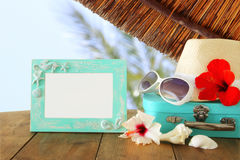 Fedora hat, sunglasses, tropical hibiscus flower next to blank frame over wooden table and beach landscape background. Relaxation or vacation concept. For royalty free stock images