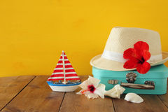 Fedora hat, sunglasses, tropical hibiscus flower on wooden table Royalty Free Stock Photography