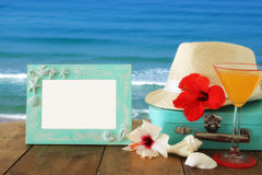Fedora hat, tropical hibiscus flower next to blank frame over wooden table and beach landscape background royalty free stock photos