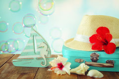 Fedora hat, tropical hibiscus flower on wooden table. relaxation or vacation concept Royalty Free Stock Image