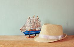 Fedora hat and wooden boat over wooden table and blue background. relaxation or vacation concept Royalty Free Stock Photos